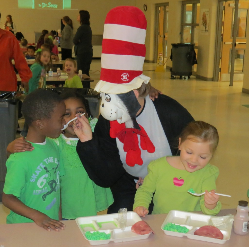 "Pictured:  ""The Cat in the Hat"" encourages some kindergarten students to try their green eggs and ham during breakfast."