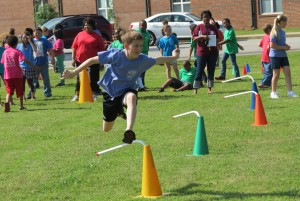 Pictured:  Students have fun jumping hurdles in a relay race.