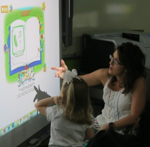 Pictured:  Business Fundamentals Instructor Alison Moore assist a PreK student in completing an interactive gardening activity on the Smartboard.