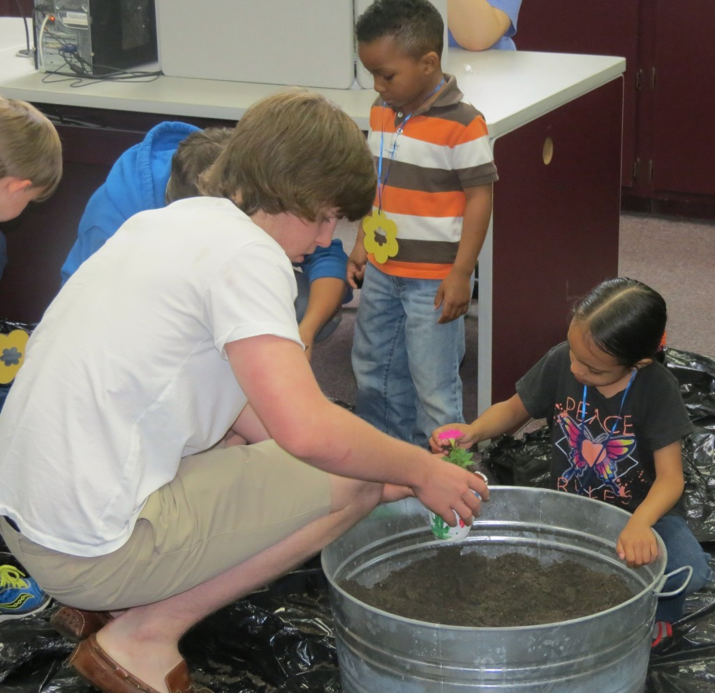 Pictured:  AEST student Holt Garrett helps PreK students in potting a plant.  The potting activity was funded by the New Albany Garden Club as part of their Young Gardeners project.
