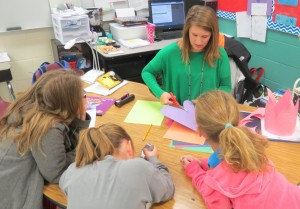 Elizabeth Day helps a group of students prepare props for Readers' Theater during a before school session.