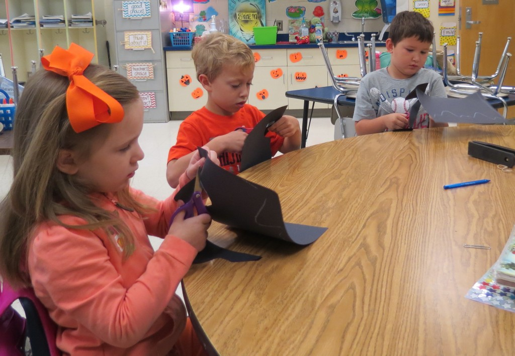 A group of elementary students work on a bat craft during before school enrichment time.  These students have been studying bat facts during the month of October.