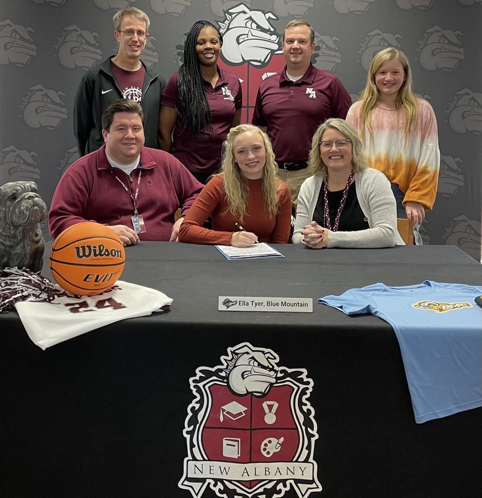 Ella Tyer signing with Blue Mountain College basketball - surrounded by family, coaches, and school administration.
