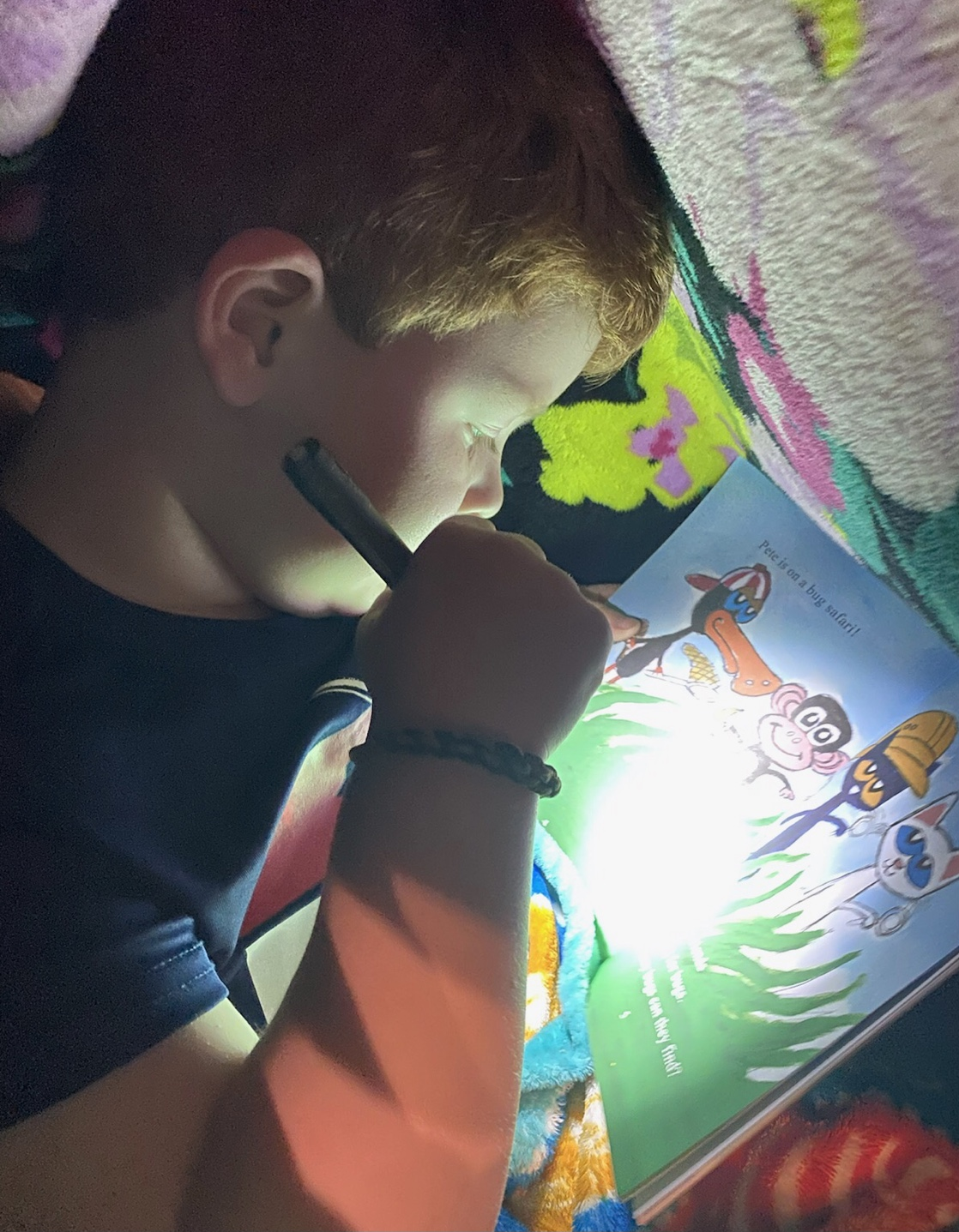 Boy reading with flashlight under blanket to complete reading challenge