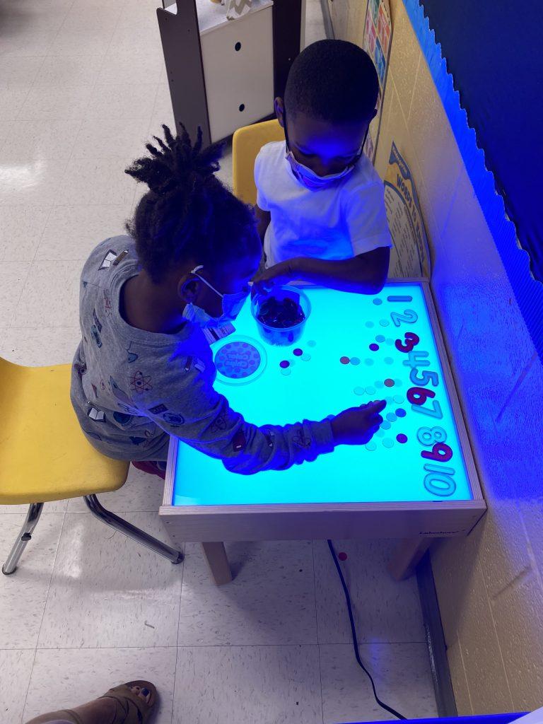Kindergarten students using light table