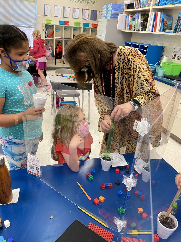 Cathy Brown, teacher assistant, is working with students Aleah Conley and Jenna Crum on measurement.