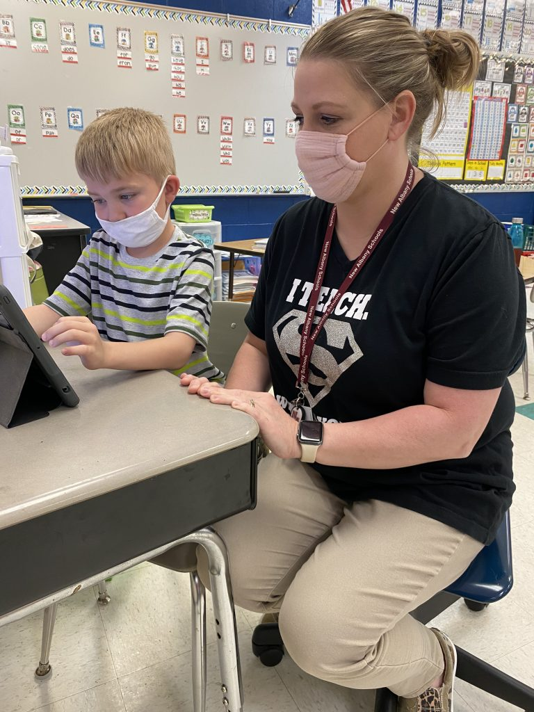 First Grade Teacher Christy Littlejohn assists Brantley Phillips in creating a Google Slides presentation that documents his plant's growth.